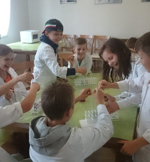 eksperyment chemiczny dzieci w fartuszkach